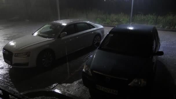 Genichesk, Ukrajina - 28. srpna 2020: Zpomalený pohled na bílé elegantní auto a černé elegantní auto umístěné na parkovišti mezi domy pod těžkou sprchou v noci na podzim ve zpomaleném filmu.