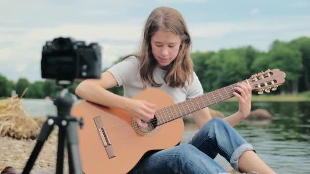Teen Girl dreht einen Blog über Musik und Online-Gitarrenspiel in der Natur vor der Kamera, die Idee von Hobbys