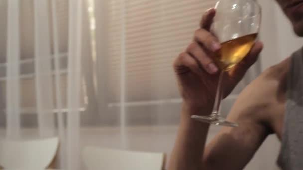 junger Mann trinkt Whiskey-Champagner aus einem Glas