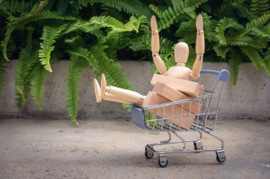 Shopping concept., Mini human model is sitting in trolley basket.