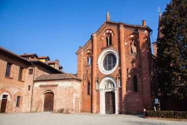 Abbey of Viboldone, in the province of Milan, with the historic main door and columns. Church of Viboldone, with bell tower, arches, statues and trees during a sunny day in the countryside of Milan.
