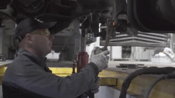 auto mechanik opravuje nákladní podvozek