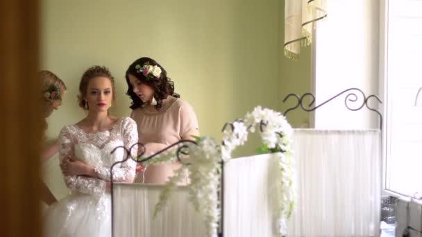 Két barátnő segít a menyasszony ruha. Mindenki mosolyog, a lányok díszítik virágok.