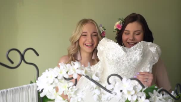 Bridesmaids are playing with a wedding dress.
