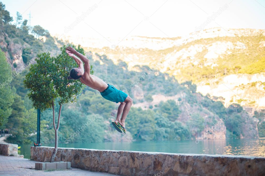 Young man doing a side flip or somersault while practicing parkour on a lake in the countryside.