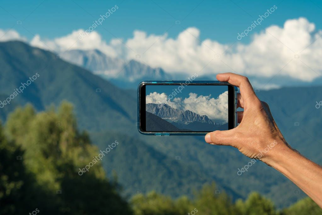 Hand making photo with smartphone camera closeup, view tourist hands using gadget phone in travel on background mountains and landscape.
