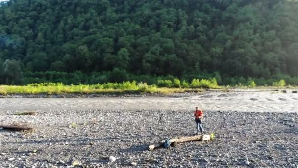 Aerial drone footage of Photographer travels and takes pictures. Location: river in the mountains. Photographer shooting nature with professional camera