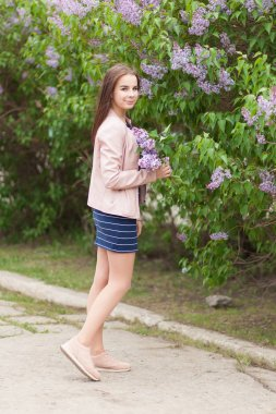 Young beautiful girl stands near the bushes of blooming lilac