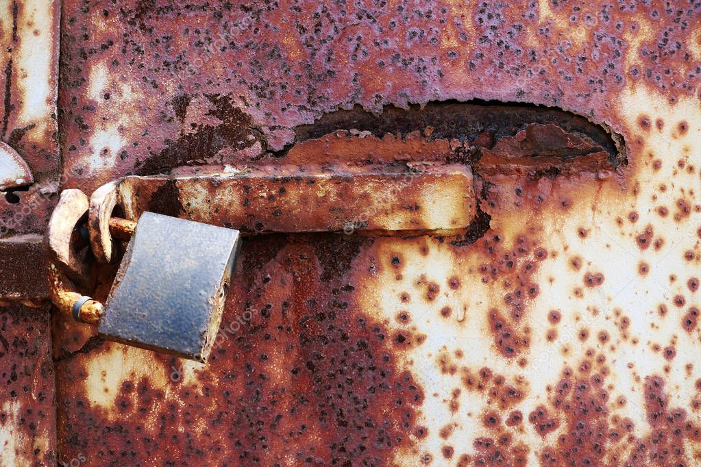 Rusty old lock on red grungy background, textplace