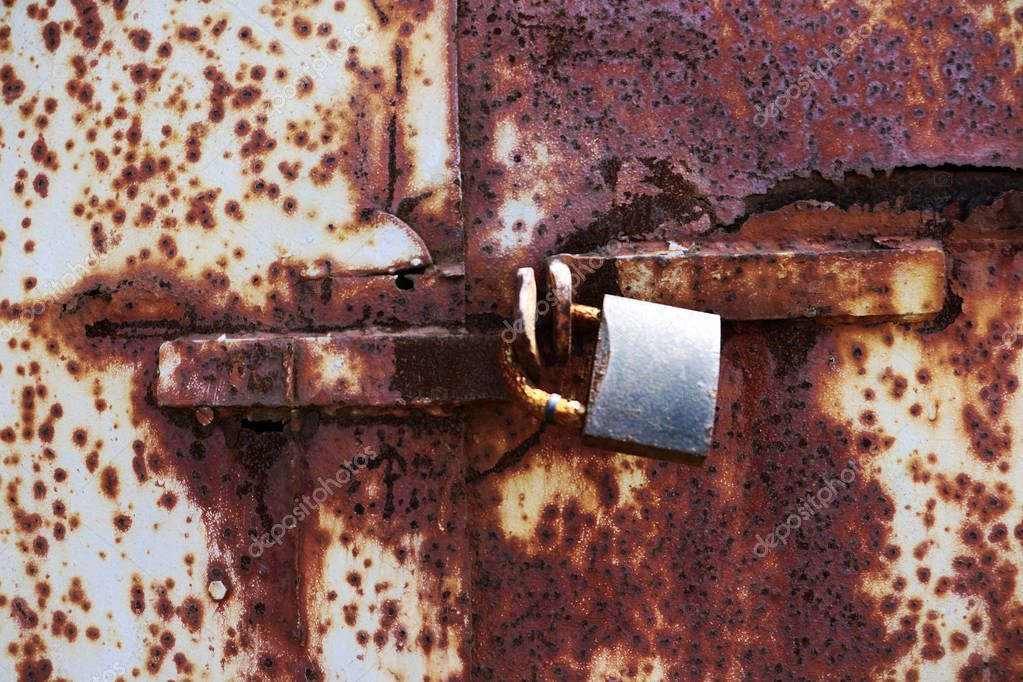 old rusted lock on a white and brown rusty gate. Rusty old lock on red background, place for text.