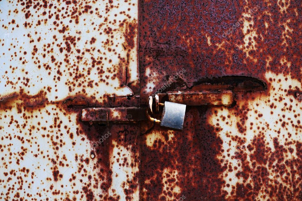 old rusted lock on a white and brown rusty gate
