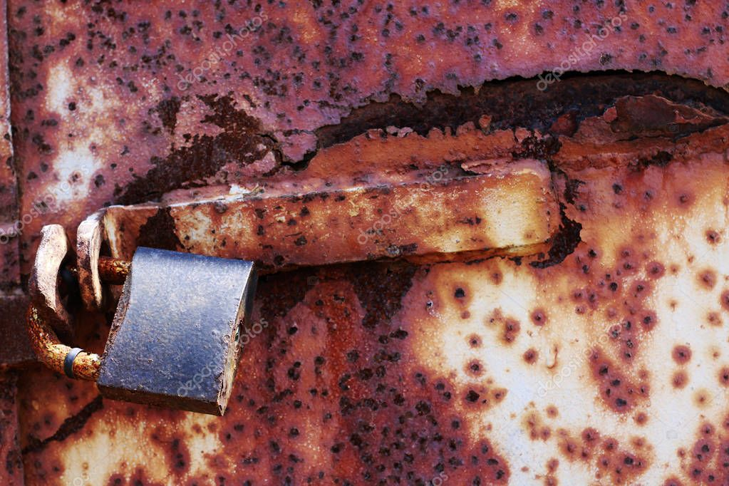 Rust old lock on red grungy background, textplace
