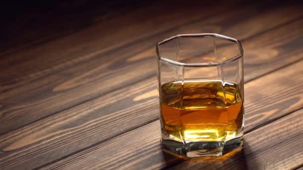 Eiswürfel fällt in Glas mit Whiskey