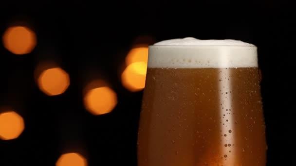 sklenice piva s pěnou a bublinkami se otáčí