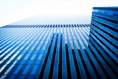 Low angle view skyscraper reflective glassy walls and windows background. Modern architecture pattern concept.