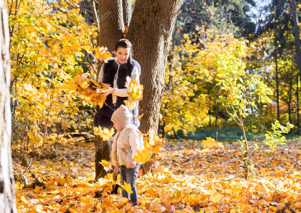 photo of mom and daughter toss the autumn leaves upwards