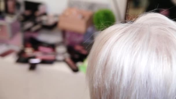 The stylist does the hairstyle for short gray hair. Video