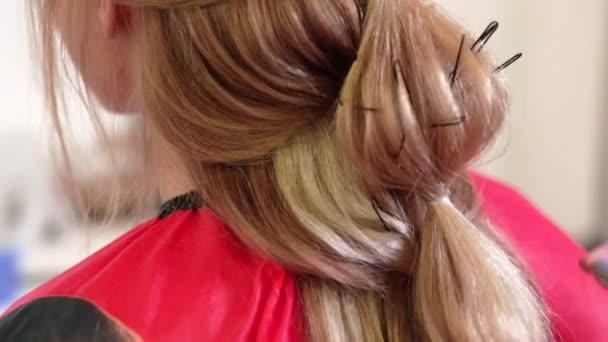 Kadeřník dělá svatební účes pro dlouhé vlasy