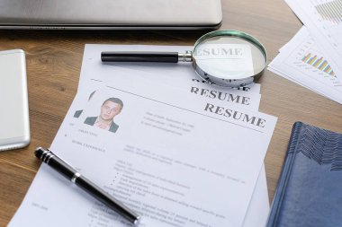 Resume (curriculum vitae, cv) and pen on a written wooden table.