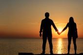 Fotografie Dva milenci (mládež) stojíte na mostě (lůžko) a drželi se za ruce, při pohledu na moře při západu slunce