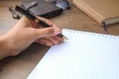 Žena (dívka, bussineswoman) ruka s perem, psaní na notebooku.