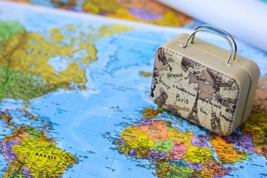 World map, drawings and suitcase. Travel and tourism.