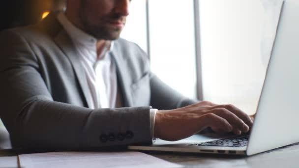 elegantní mladý podnikatel v šedém obleku psaní na notebooku