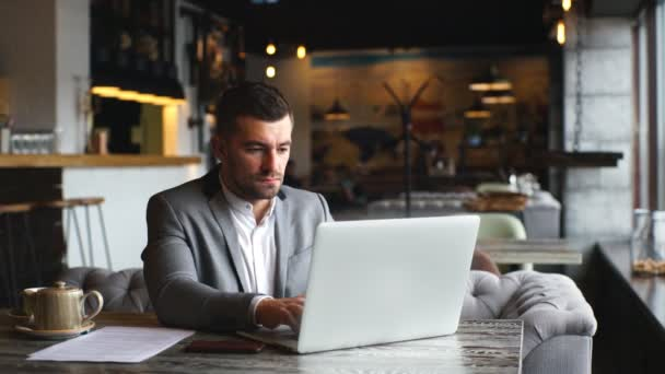 Young bearded businessman wearing grey suit,sitting at table in cafe and using laptop