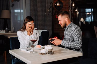 Portrait of happy and surprised young woman receiving present from boyfriend while sitting in cafe