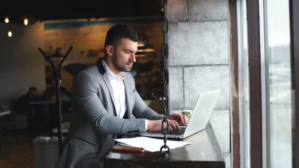 mladý pohledný atraktivní vousatý podnikatel sedí u stolu v obleku a psaní na notebooku s mobile poblíž
