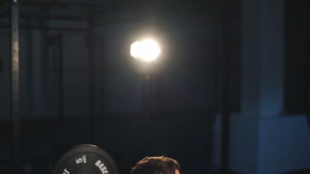 člověk dělá dřepu s váhami v tělocvičně