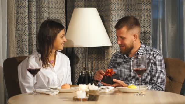 a beautiful couple in love exchanges gifts for Valentines day, a date in a cafe