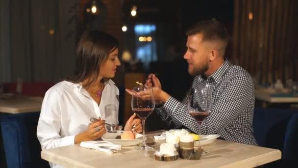 mladý pár v restauraci na večeři. Mladý muž živí svou přítelkyni s cheesecake a smích