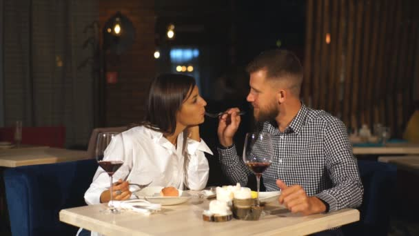 young couple on a date. A man feeds his woman a delicious dessert. Couple laughing in the restaurant