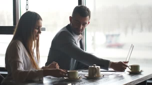 Businessman and woman working with documents and discussing business plans