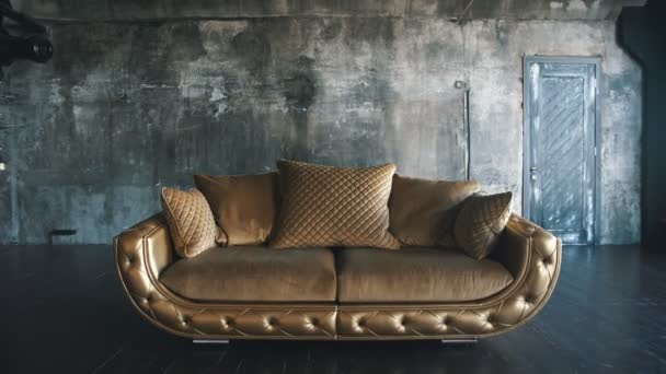 Luxurious sofa in a modern interio. In dark tones and shades of gold
