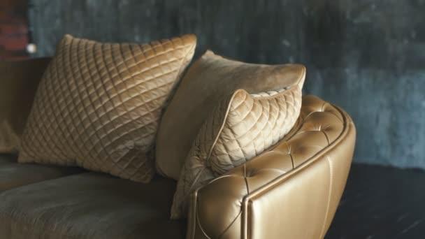Luxusní zlaté pohovka na podkroví background.luxury prošívaná pohovka v Studio ve zlaté barvě, luxusní zlaté pohovka na pozadí podkroví. Krásná pohovka v okně v moderním bytě