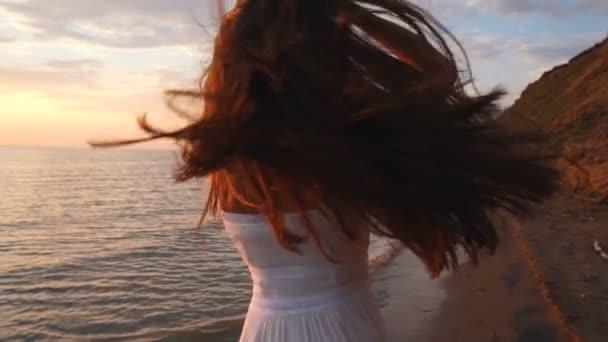 ein Mädchen im weißen Kleid tanzt am Strand