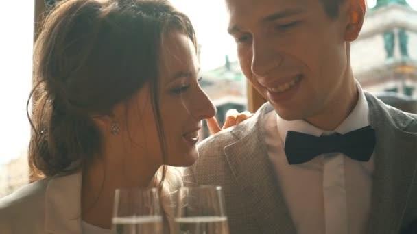 Frischvermählte küssen und trinken Champagner im Restaurant