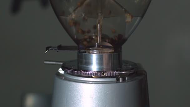Kávové zrno v mlýnku, Close-up pražené zrnkové kávy v kávovaru