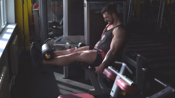 Handsome man at the gym doing exercises on leg