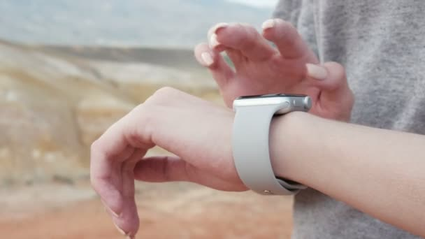 Woman making gestures on a wearable smartwatch computer device, smart watch. Sunny day. Closeup. Smart watch on female wrist. Outdoors