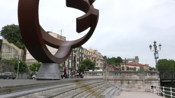BILBAO, SPAIN - circa 2017: Bilbao Town Hall , traffic cars, people and and sculpture Variante Ovoide de la Desocupacion de la Esfera in Bilbao, Spain. The sculpture was designed by Jorge Oteiza