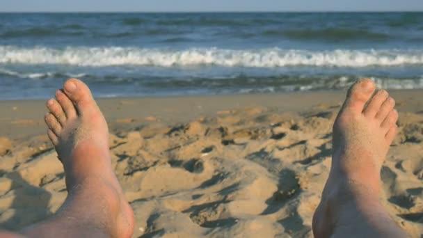 Muž nohy opalování na pláži na pozadí písek a modré moře s vlnami, chlape bosé nohy na pláži