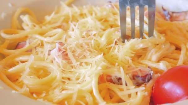 Eating close up of Italian pasta carbonara with parmesan and bacon.
