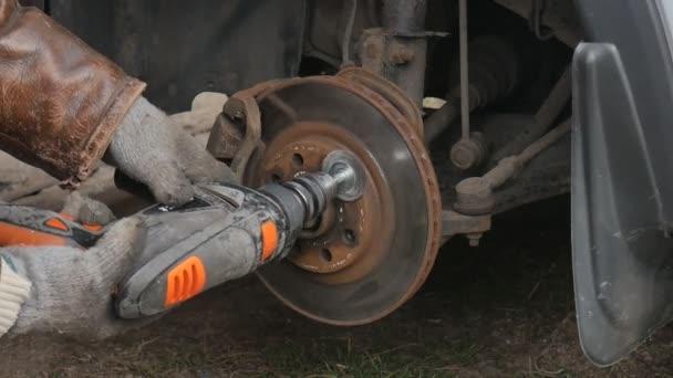 Samec čistí elektrický vrták z korozní brzdy před výměnou kotouče.