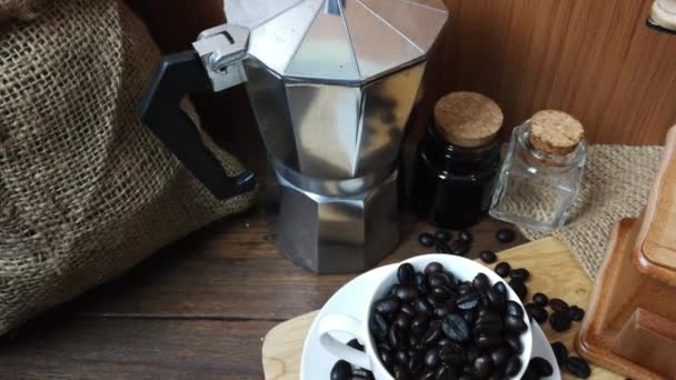 Coffee cup and coffee beans on wooden background footage.