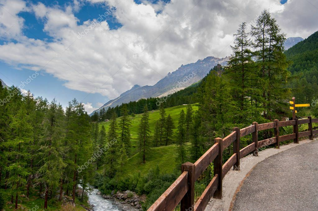 Alpine scenery with river and road fence