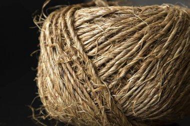 Skein of jute twine on black background, close up, macro
