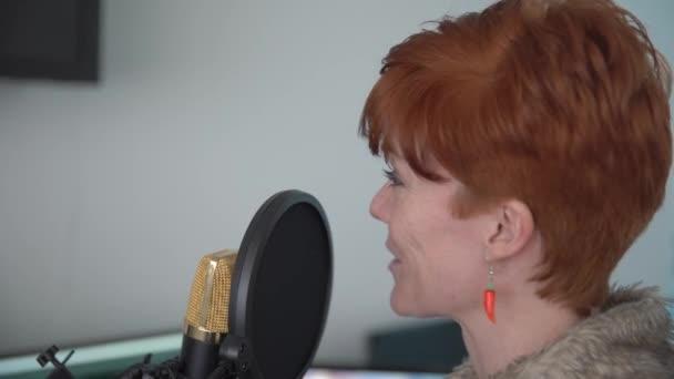 Fiatal nő a stúdióban a hangmintát kereskedelmi projektek, a stúdió mikrofon